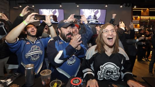 Ryan Kelly, left, Otto Rogers and Rebecca Moloney cheer the announcement of a new NHL hockey team in Seattle at a celebratory party Tuesday, Dec. 4, 2018, in Seattle.