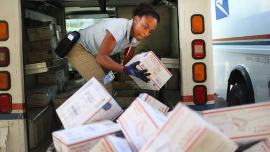 A City Carrier Assistant to the United States Postal Service, unloads her mail truck after collecting mail on the busiest mailing day of the year for the U.S. Postal Service in Miami, Florida.