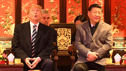 US President Donald Trump (L) looks up as he sits beside China's President Xi Jinping (R) during a tour of the Forbidden City in Beijing on November 8, 2017.