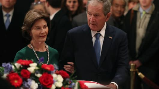 Former U.S. President George W. Bush and his wife Laura Bush pay their respects in front of the casket of the late former President George H.W. Bush as he lies in state in the U.S. Capitol Rotunda, December 4, 2018 in Washington, DC.