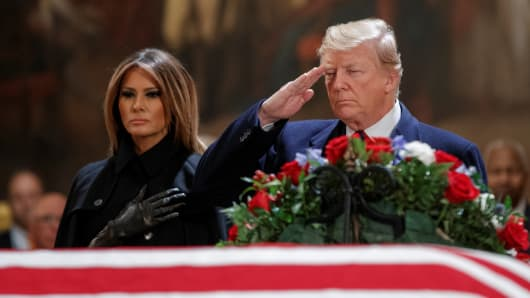 President Donald Trump and first lady Melania Trump pay their respects to former President George H.W. Bush as he lies in state in the US Capitol's rotunda December 3, 2018.