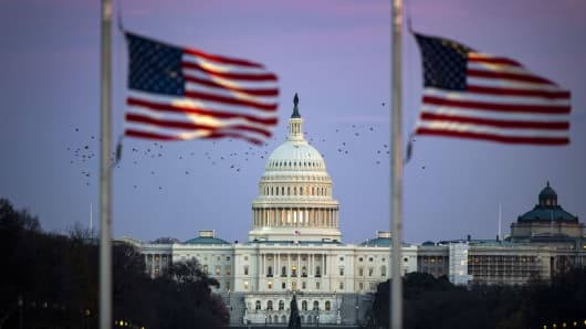 The U.S. Capitol is seen through American flags flying at half staff as former U.S. President George H.W. Bush lies in state at the Capitol Rotunda, Dec. 3, 2018.