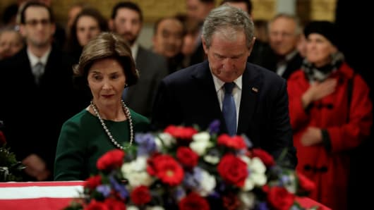 Former President George W. Bush and former first lady Laura Bush stand at the flag-draped casket of former U.S. President George H.W. Bush as it lies in state inside the U.S. Capitol Rotunda, December 4, 2018.
