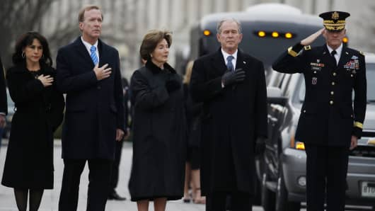 From right, former President George W. Bush, second from right, former first lady Laura Bush, Neil Bush and Sharon Bush, stand as a joint services military honor guard carries the flag-draped casket of former U.S. President George H. W. Bush from the U.S. Capitol to transport it to Washington National Cathedral.