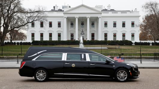 The hearse carrying the flag-draped casket of former President George H.W. Bush passes by the White House from the Capitol.