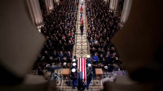The flag-draped casket of former President George H.W. Bush arrives carried by a military honor guard during a State Funeral at the National Cathedral.