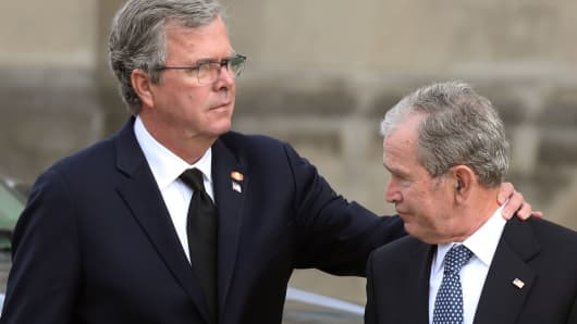 Former President George W. Bush (R) and his brother, former Florida Governor Jeb Bush, arrive for the funeral service for their father, former President George H. W. Bush, at the Washington National Cathedral.
