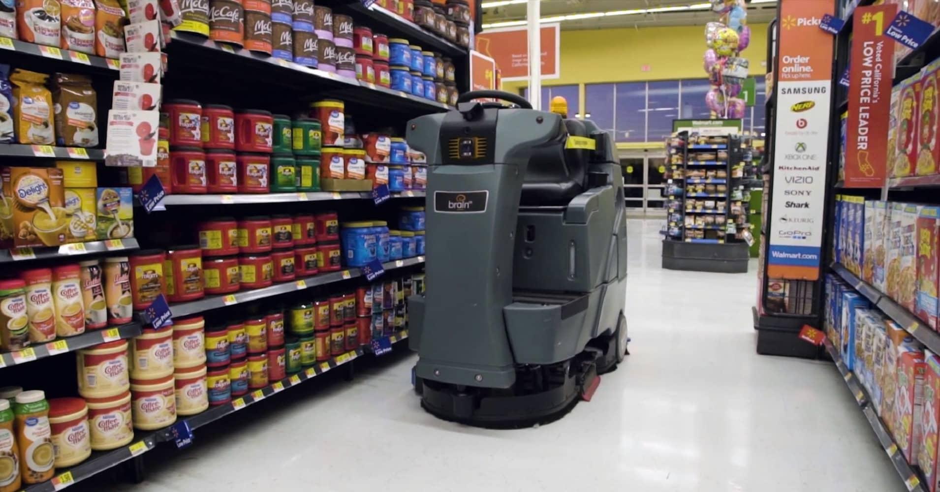 A Brain Corp. autonomous floor scrubber, called an Auto-C, cleans the aisle of a Walmart store.