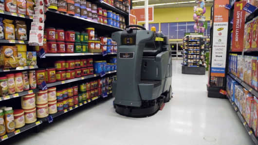 A Brain Corp. autonomous floor scrubber, called an Auto-C, cleans the aisle of a Walmart store.