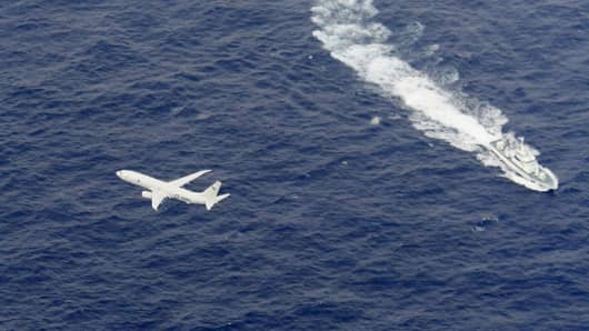 A Japan Coast Guard patrol vessel and U.S. Navy airplane conduct search and rescue operation at the area where two U.S. Marine Corps aircraft have been involved in a mishap in the skies, off the coast of Kochi prefecture, Japan, in this aerial view photo taken by Kyodo December 6, 2018.