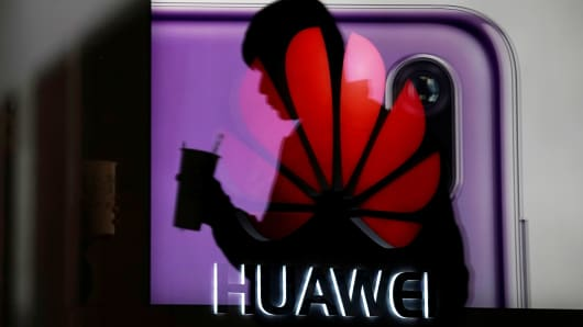 A man walking suits a Huawei P20 smartphone advertisement is reflected in a glass by in front of a Huawei logo, at a shopping mall in Shanghai, China December 6, 2018.