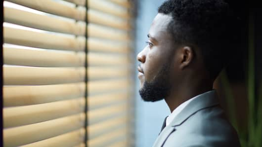 Pensive handsome young African man with beard looking through blinds while thinking about new project in corridor