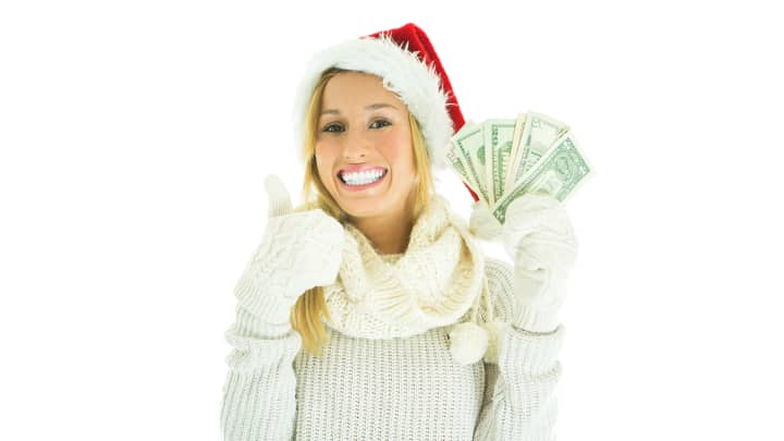 Cheerful woman at christmas with money in hands