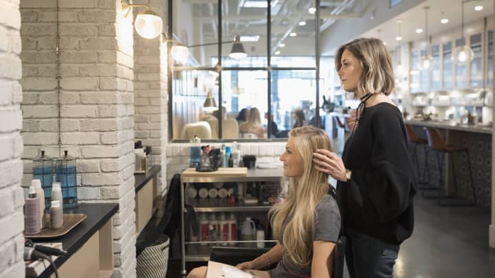Female hair stylist and customer talking, planning in hair salon