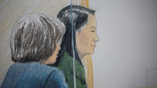 Huawei CFO Meng Wanzhou, who was arrested on an extradition warrant, appears at her B.C. Supreme Court bail hearing along with a translator, in a drawing in Vancouver, British Columbia, Canada December 7, 2018.