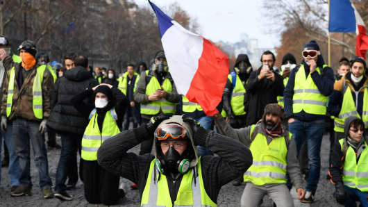 Protestors wearing 'yellow vests' (gilet jaune) kneel on the Champs Elysees avenue in Paris on December 8, 2018 during a protest against rising costs of living they blame on high taxes.