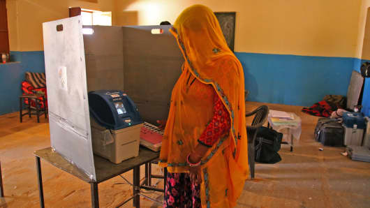 An Indian woman casts her vote at a local polling station for state elections in the village of Raisar in Rajasthan on Dec 7, 2018.