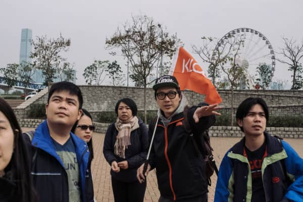 A tour guide, center right, holds a flag while introducing a location to a group of tourists during a guided walking tour hosted by Klook Travel Technology Ltd. in Hong Kong.