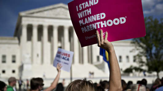 """A demonstrator opposed to the Senate Republican health-care holds a sign that reads """"I Stand With Planned Parenthood' while marching near the U.S. Supreme Court in Washington, D.C."""