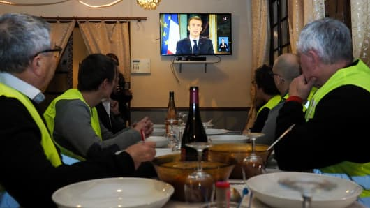 Yellow vest (gilets jaunes) protestors take notes as thet watch French President Emmanuel Macron's speech on TV on December 10, 2018 at a restaurant with French deputy Richard Damos, in Fay-au-Loges, near Orleans, Center France.