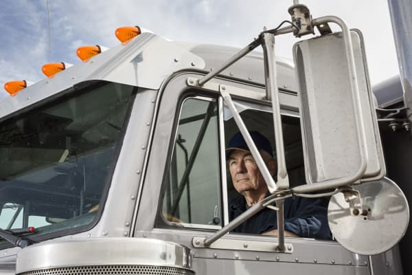 Caucasian trucker sitting in semi-truck