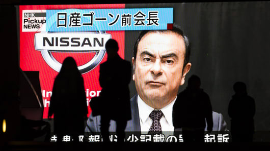 Pedestrians walk in front of a monitor showing an image of former Nissan Motor Co. Chairman Carlos Ghosn in a news program on December 10, 2018 in Tokyo, Japan.