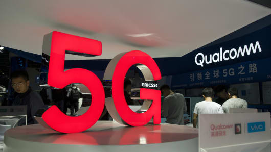 Attendees look at 5G mobile phones at the Qualcomm stand during China Mobile Global Partner Conference 2018 at Poly World Trade Center Exhibition Hall in Guangzhou, China.