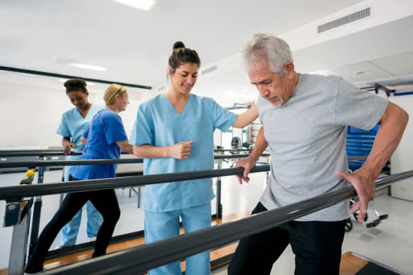 Diverse team of physiotherapist helping patients walk between parallel bars