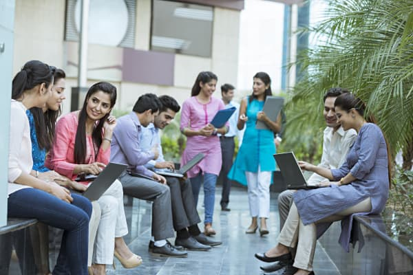 Business people sitting in office courtyard and discussing
