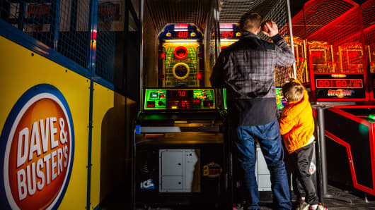 Customers play a basketball arcade game at a Dave & Buster's Entertainment Inc. location in Pelham, New York.
