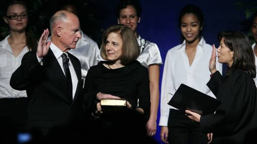 Jerry Brown (L) is sworn in as the 39th governor of California by California Chief Justice Tani CAntil-Sakauye (R) as Brown's wife, Anne Gust-Brown (C), looks on  January 3, 2011 in Sacramento, California.