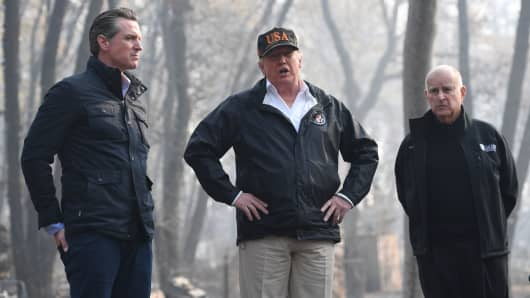 US President Donald Trump (C) looks on with Governor of California Jerry Brown (R) and Lieutenant Governor of California, Gavin Newsom, as they view damage from wildfires in Paradise, California on November 17, 2018.