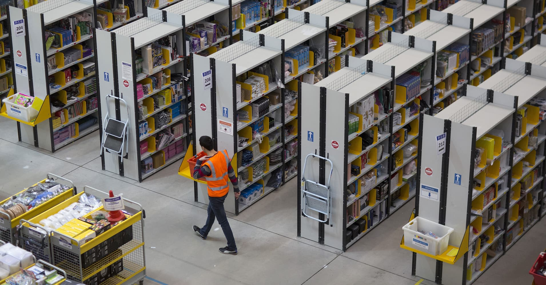 An employee walks between rows of storage racks at one of Amazon.com's fulfillment centers in Rugeley, U.K.