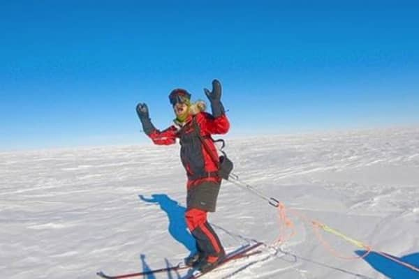 Colin O'Brady celebrates in the snow.