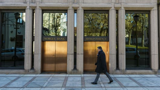 A pedestrian passes the closed entrance to the headquarters of Norges Bank, also known as the central bank, in Oslo, Norway, on Wednesday, Oct. 29, 2014.