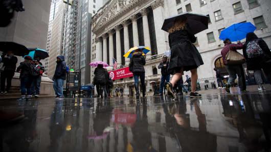 Pedestrians carrying umbrellas walk past the New York Stock Exchange.