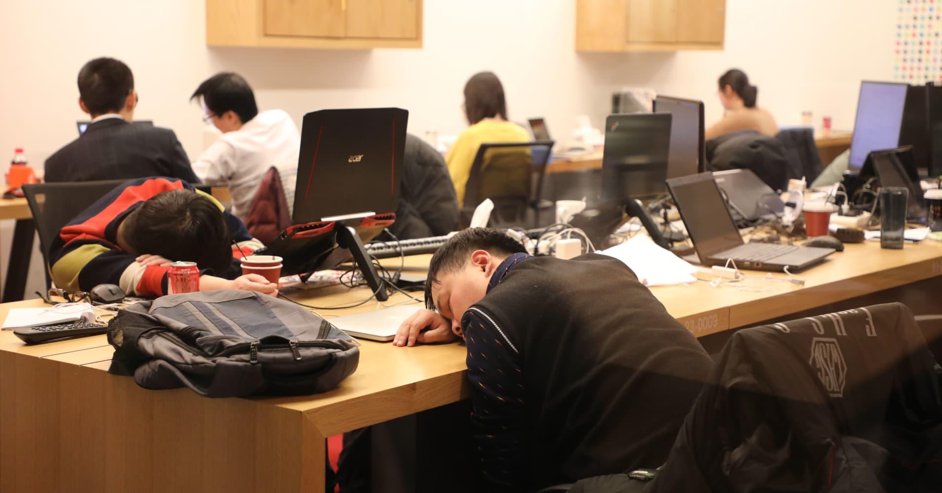 People sleep on desks at a start-up incubator in Beijing on January 9, 2018.