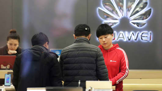 A saleswoman serves customers at a Huawei shop in Beijing, China, December 12, 2018.