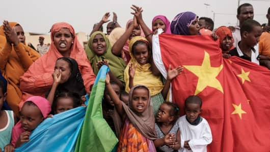 People hold Chinese and Djiboutian national flags to celebrate a new housing construction project in Djibouti, on July 4, 2018.