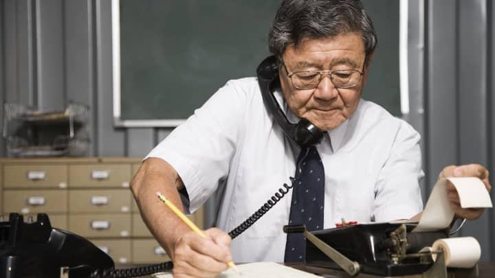 Senior Asian businessman using old fashioned adding machine