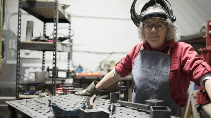Portrait confident senior female welder at workbench in workshop