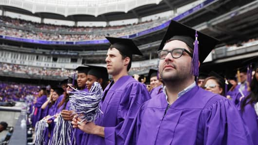Graduating students attend New York University's commencement ceremony at Yankee Stadium.