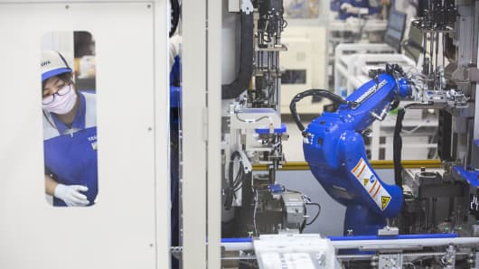A Yaskawa Electric Corp. employee monitors a Motoman robot operating on the servomotor assembly line at the company's Solution Factory in Iruma, Saitama Prefecture, Japan, on Monday, Dec. 3, 2018.