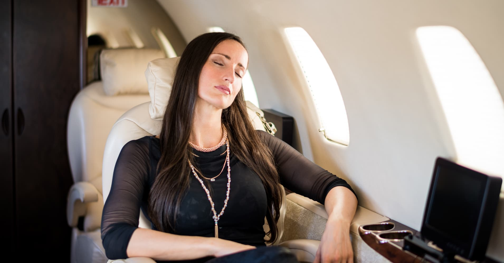 A woman taking a very expensive nap in first class.