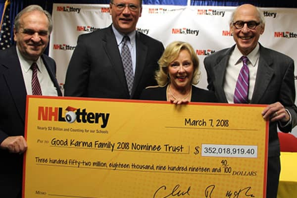 Representatives of theGood Karma Family 2018 Nominee Trust accept a check from the New Hampshire Lottery.