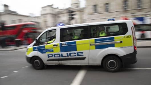 Metropolitan police van passes at speed on Whitehall in London, United Kingdom.