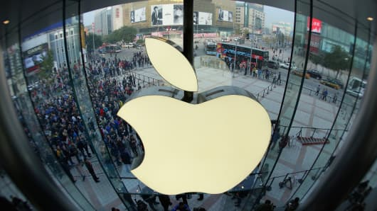 Apple staff members celebrate as customers coming the Wangfujing store on October 20, 2012 in Beijing, China.