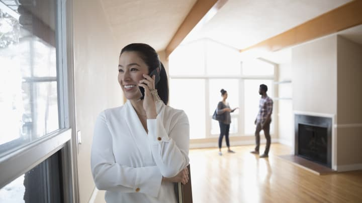 Smiling, confident realtor talking on smart phone, showing new house to young couple