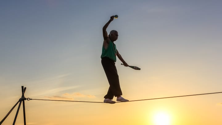 Key West, Florida, United States - April 13, 2012: a tightrope walker tosses of skittles. Show of street artists that takes place every day during the sunset celebration at Mallory Square in Key West.