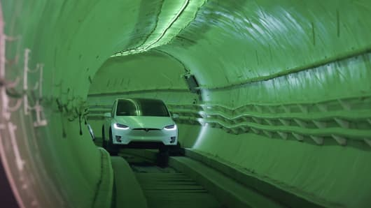 A modified Tesla Model X electric vehicle carrying Elon Musk, co-founder and chief executive officer of Tesla Inc., drives through the tunnel as it arrives for an unveiling event for the Boring Co. Hawthorne test tunnel in Hawthorne, California, U.S., on Tuesday, Dec. 18, 2018.
